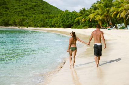 honeymoon couple holding hands and walking along a Caribbean bea
